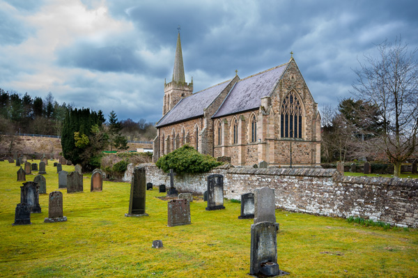 St Cuthbert's Church and surrounding graveyard, beneath a moody cloud filled sky